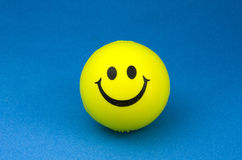 Happy smiley. Yellow smiley face on blue background Stock Image