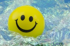 Happy smiley. Happy yellow smiley face over a bright pearly background Royalty Free Stock Photo