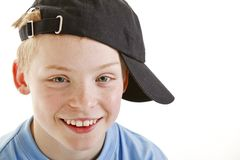 Happy smiling 12 year old boy with a cap isolated Stock Photos