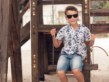 Happy smiling adolescent boy in sunglasses  on a swing Stock Photos