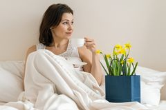 Happy smiling adult woman with bouquet of yellow flowers and cup of coffee sitting at home in bed.  stock photo