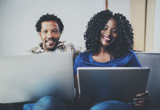 Happy smiling african american couple using mobile gadgets,laptop at home while sitting on the sofa. Horizontal,blurred Royalty Free Stock Image