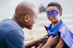 Happy smiling African American son being supported and helped by supportive father. For little adventure and protection stock images