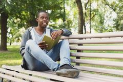 African-american student reading a book outdoors. Happy smiling african-american student reading a book in the park, studying and preparing for exams at the Royalty Free Stock Photography