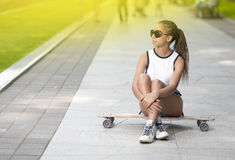 Happy Smiling African American Teenage Girl With Long Board Posing in Park Royalty Free Stock Photo