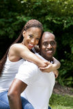 Happy smiling African couple. Beautiful happy smiling laughing young African American couple piggyback playing in the park, woman hugging man, wearing white stock image