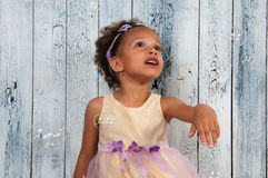Happy smiling african  girl blowing soap bubbles on the background of wooden wall Stock Photos