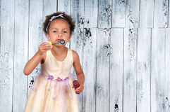 Happy smiling african  girl blowing soap bubbles on the background of wooden wall Stock Photography