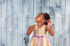 Happy smiling african  girl blowing soap bubbles on the background of wooden wall Stock Image