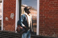 Happy smiling african man in jeans jacket, with backpack looking up at sunlight walking on city street over brick wall stock images