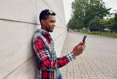 Happy smiling african man with smartphone on city street, gray brick wall stock image