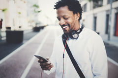 Happy smiling African man using smartphone outdoor.Portrait of young black cheerful man texting a sms message with Royalty Free Stock Photo