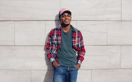 Happy smiling african man wearing red plaid shirt, baseball cap posing on city street, gray brick wall royalty free stock images