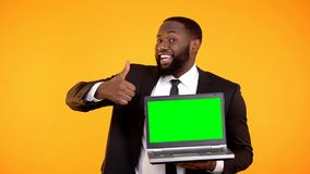 Happy smiling afro-american male showing prekeyed laptop and thumbs-up gesture. Stock photo stock photos