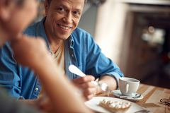 Happy smiling aged man looking to female. Enjoyable meeting. Close up portrait of happy smiling aged male looking with pleasure to lady while meeting in cafe royalty free stock image