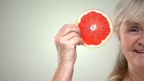 Happy smiling aged woman showing slice of juicy grapefruit, half-face closeup stock photos