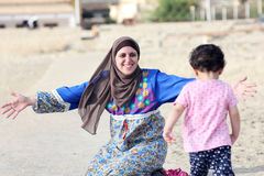Happy smiling arab muslim mother hug her baby girl in egypt. Photo of happy smiling arabian egyptian mother hug her baby girl on their way to local beach in Stock Image