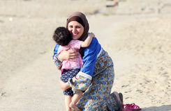 Happy smiling arab muslim mother hug her baby girl. Photo of happy smiling arabian mother hug her baby girl in local beach in egypt Stock Images
