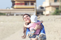 Happy smiling arab muslim mother wearing islamic hijab hug her baby girl in egypt. Photo of happy smiling arabian egyptian mother hug her baby girl on their way stock photo