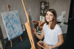 Happy smiling Artist painter young beautiful girl. Working creating process. painting on easel. inspired work stock photography