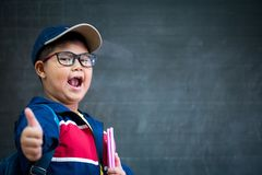 Happy smiling asian boy in glasses with thumb up. Is going to school for the first time. Child with school bag and book on blackboard background. Back to school Stock Images
