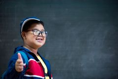 Happy smiling asian boy in glasses with thumb up. Is going to school for the first time. Child with school bag and book on blackboard background. Back to school Royalty Free Stock Image