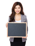 Happy smiling Asian business girl holding blank blackboard Stock Image