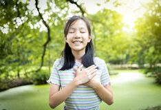 Happy smiling asian child girl standing in green nature,hold hands on heart,feel peace of mind,female teenage closed eyes,enjoy