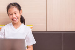 Happy smiling asian girl using notebook computer to study on her Stock Photos