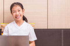 Happy smiling asian girl using notebook computer to study on her Royalty Free Stock Photos