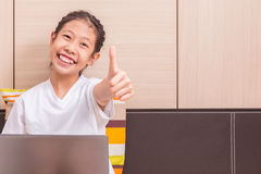 Happy smiling asian girl using notebook computer to study in her Royalty Free Stock Photo