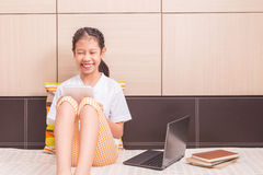 Happy smiling asian girl using tablet computer to study on her b Stock Images