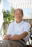 Happy Smiling Asian Senior Sitting at Backyard Royalty Free Stock Images