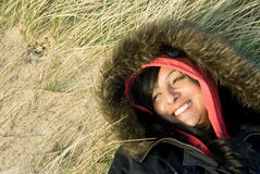 Happy smiling asian woman. Colour portrait photo of a happy smiling asian woman in her thirties laying on her back on the beach while wearing a hooded winter Stock Photo