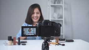 Happy smiling asian woman or beauty blogger with brush and camera recording video and waving hand at home. stock footage