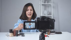 Happy smiling asian woman or beauty blogger with brush and camera recording video and waving hand at home.
