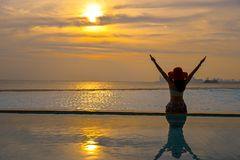 Happy smiling asian woman with straw hat relax and luxury in swimming pool, background sunset. Stock Images