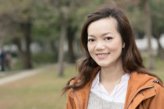 Happy smiling Asian young woman in the park Royalty Free Stock Image
