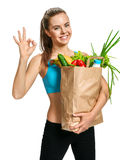 Happy smiling athletic woman showing okay gesture with grocery bag full of healthy fruits and vegetables Royalty Free Stock Photography