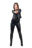 Happy smiling attractive woman in black leather pointing gun at camera Stock Image