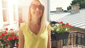 Happy smiling attractive woman with sunglasses on sunny romantic balcony stock video