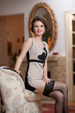 Happy smiling attractive woman wearing an elegant dress and black stockings sitting on the sofa arm. Beautiful young sensual girl Royalty Free Stock Photography