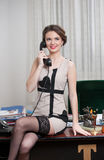 Happy smiling attractive woman wearing an elegant dress and black stockings talking by phone in an office scenery. Beautiful girl Royalty Free Stock Images