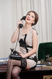 Happy smiling attractive woman wearing an elegant dress and black stockings talking by phone in an office scenery. Beautiful girl Royalty Free Stock Image