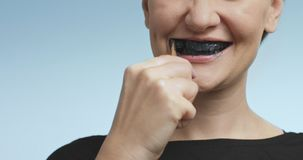 Pretty young woman brushing her teeth with black toothpaste Royalty Free Stock Image