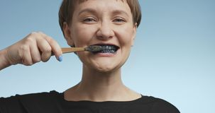 Pretty young woman brushing her teeth with black toothpaste Stock Photos