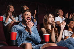 Happy smiling audience clapping hands. While sitting at the cinema and watching movie stock photo