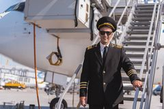 Happy smiling aviator locating near ladder. Cheerful pilot wearing sunglasses is standing on gangway and looking at camera with bright smile. Waist up portrait Royalty Free Stock Photography