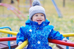 Happy smiling baby boy outdoors in autumn on playground Stock Image