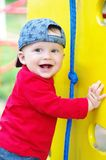 Happy smiling baby boy on playground in summertime. Happy smiling baby boy age of 11 months on playground in summertime Stock Images